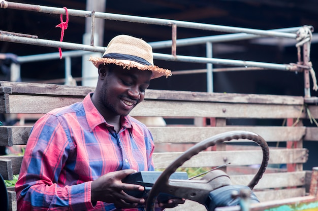 L'uomo africano dell'agricoltore con il retro ricevitore radiofonico sulla spalla sta sorridere felice all'aperto sulla vecchia automobile con fondo Foto Premium