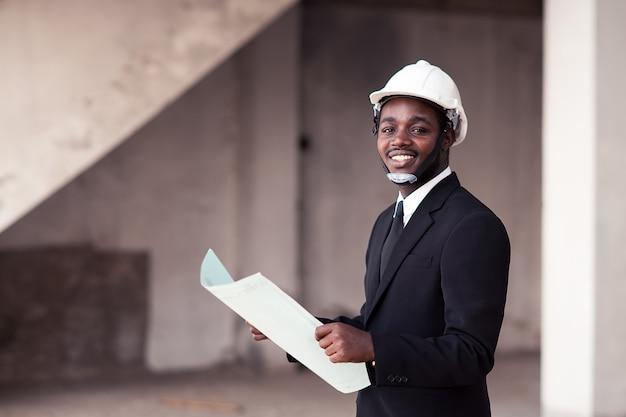 L'uomo africano dell'ingegnere si alza e smilling Foto Premium
