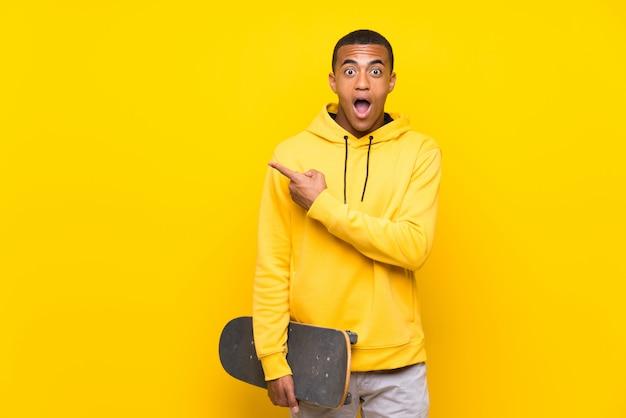 L'uomo afroamericano del pattinatore ha sorpreso e indicando il lato Foto Premium