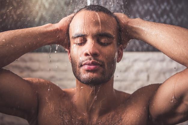 L'uomo afroamericano nudo sta facendo la doccia in bagno Foto Premium