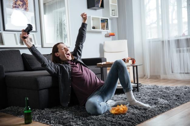 L'uomo allegro che si siede a casa all'interno gioca con la leva di comando Foto Gratuite
