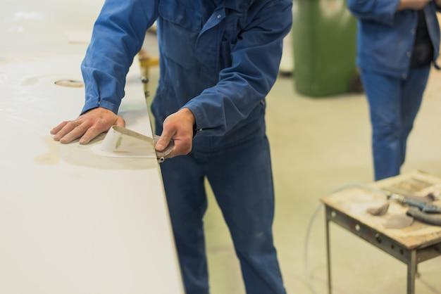 L'uomo allinea l'ala di carta vetrata. il lavoratore lucida la superficie di lavoro Foto Premium