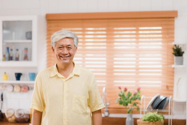 L'uomo anziano asiatico che ritiene sorridere felice e guardare alla macchina fotografica mentre si rilassa in cucina a casa. concetto degli uomini senior di stile di vita a casa. Foto Gratuite