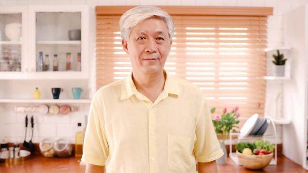 L'uomo anziano asiatico che ritiene sorridere felice e guardare alla macchina fotografica mentre si rilassa in cucina a casa. Foto Gratuite