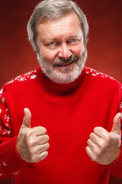 L'uomo anziano che mostra bene firma dentro il maglione rosso di natale Foto Gratuite