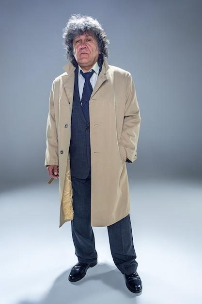 L'uomo anziano in mantello con sigaro come detective o boss mafioso. Foto Gratuite