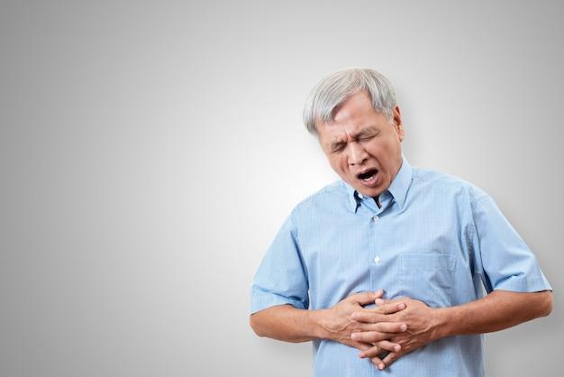 L'uomo asiatico più anziano sta avendo il concetto di dolore di mal di stomaco Foto Premium