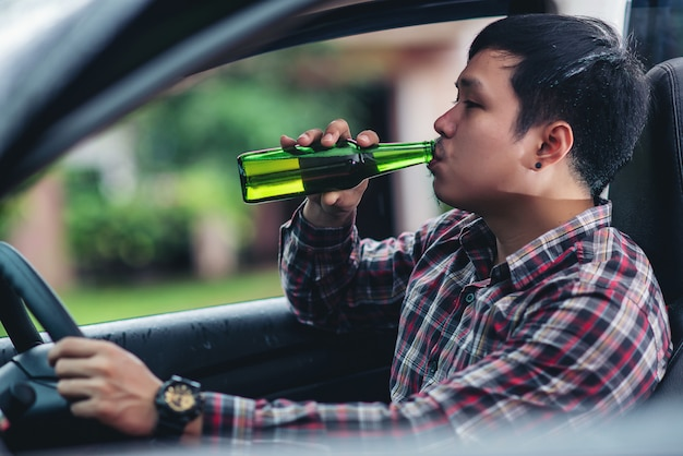 L'uomo asiatico tiene una bottiglia di birra mentre sta guidando una macchina Foto Gratuite