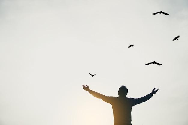 L'uomo aumenta le mani fino al cielo che esamina gli uccelli volare attraverso il concetto di libertà della metafora con il tono in bianco e nero del cielo del tramonto. Foto Premium