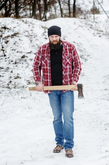 L'uomo barbuto arrabbiato con un'ascia passa attraverso la foresta dell'inverno Foto Premium
