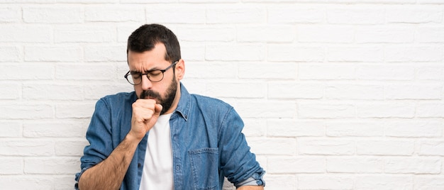 L'uomo bello con la barba sopra il muro di mattoni bianco soffre di tosse e si sente male Foto Premium