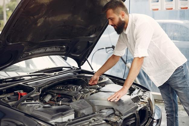 L'uomo bello controlla il motore in sua automobile Foto Gratuite