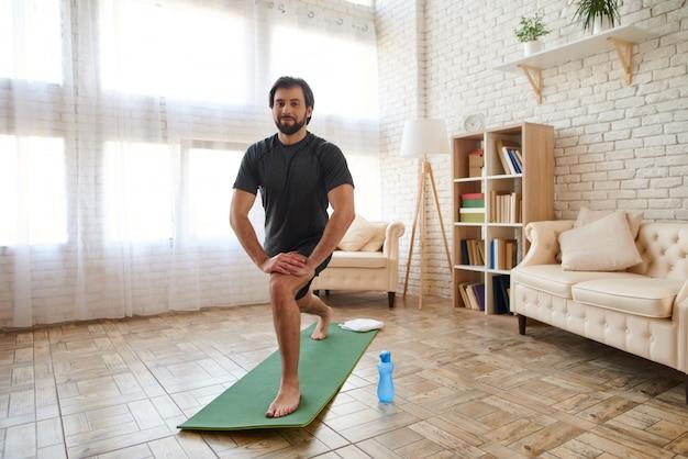 L'uomo bello fa l'allungamento dell'esercizio a casa. Foto Premium