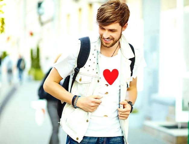 L'uomo bello sorridente divertente dei pantaloni a vita bassa in estate alla moda copre la posa sul fondo della via Foto Gratuite