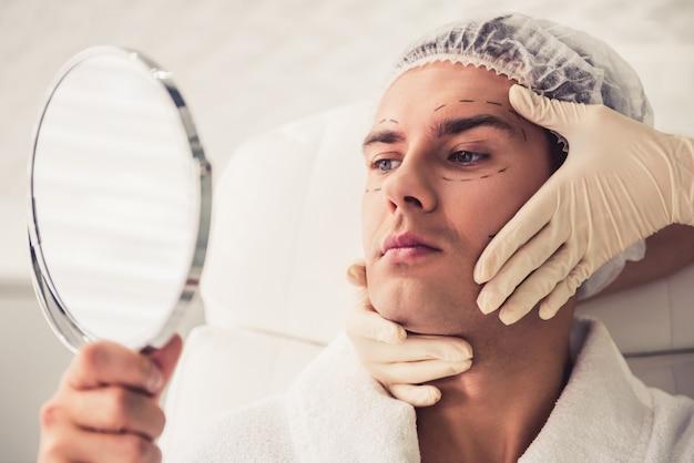 L'uomo bello sta esaminando lo specchio. Foto Premium