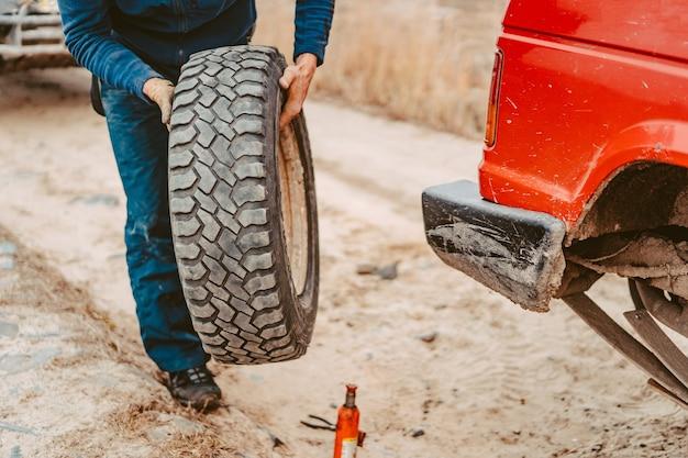 L'uomo cambia manualmente la ruota su un fuoristrada 4x4 Foto Gratuite