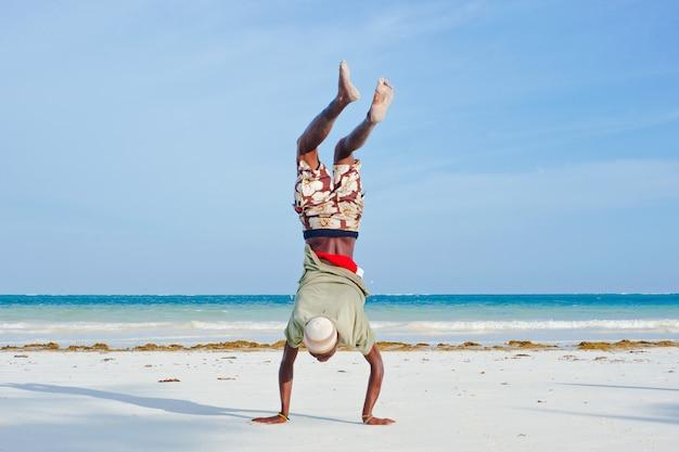 L'uomo cammina sulle sue mani. diani beach Foto Premium