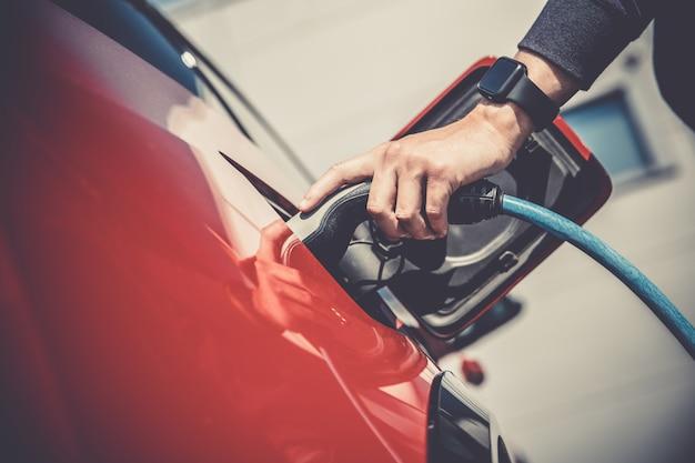 L'uomo carica l'auto elettrica alla stazione di ricarica Foto Premium