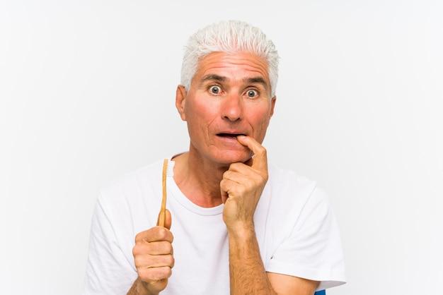 L'uomo caucasico senior che tiene uno spazzolino da denti ha isolato il pensiero rilassato a qualcosa che esamina uno spazio della copia. Foto Premium