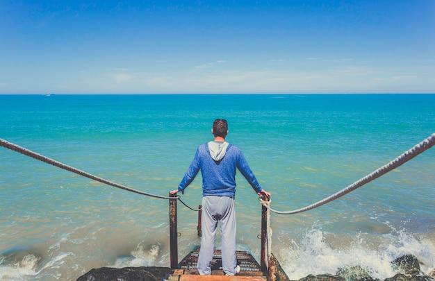 L'uomo caucasico si leva in piedi sulle vecchie scala di legno che vanno giù al mar mediterraneo Foto Premium