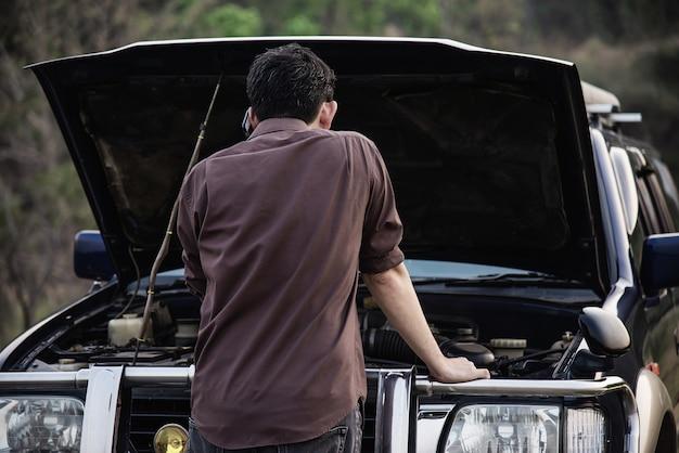 L'uomo cerca di risolvere un problema con il motore di un'auto in una strada locale Foto Gratuite