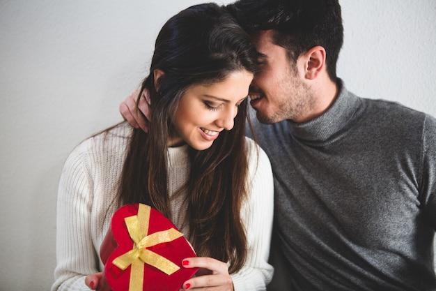 L'uomo che bisbiglia qualcosa alla sua ragazza, mentre lei tiene un regalo Foto Gratuite