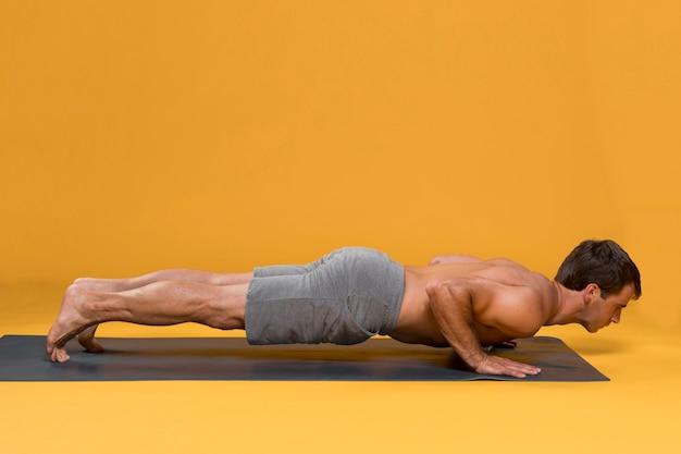 L'uomo che fa push up sulla stuoia di yoga Foto Gratuite