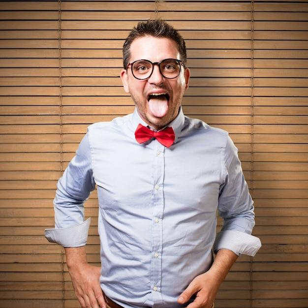 L'uomo che indossa una cravatta a farfalla rossa. tirando fuori la lingua. Foto Gratuite