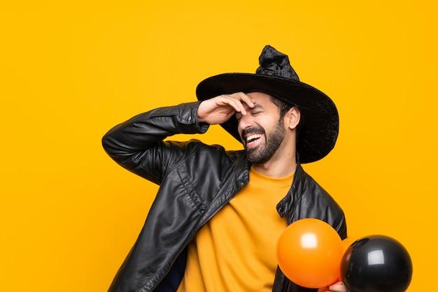 L'uomo con il cappello da strega che tiene mongolfiere nere e arancioni per la festa di halloween ha realizzato qualcosa e intendendo la soluzione Foto Premium