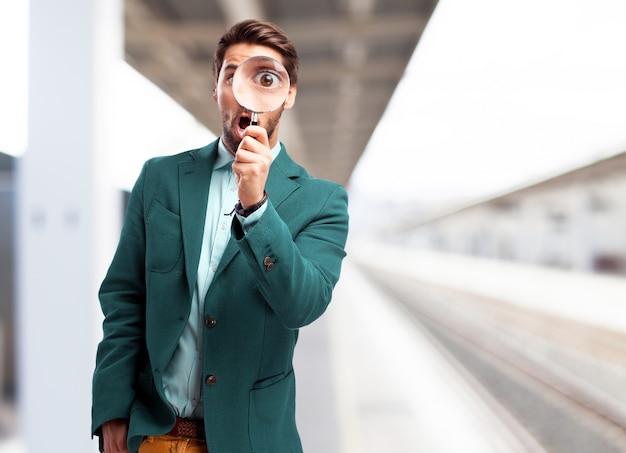 L'uomo con una lente di ingrandimento nella stazione ferroviaria Foto Gratuite