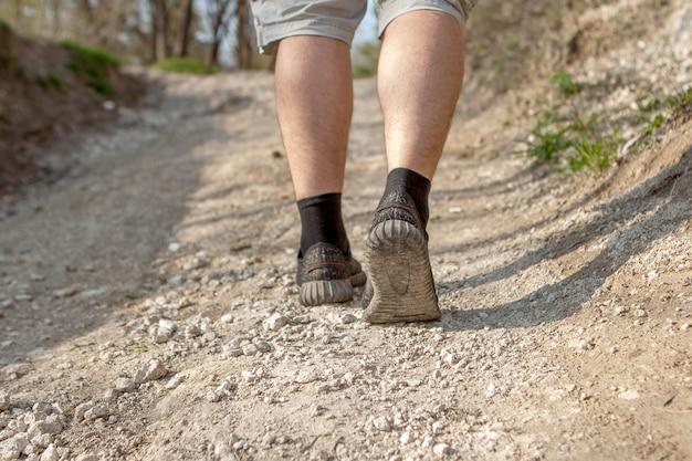 L'uomo corre lungo il sentiero. smart running attraverso la foresta. concetto di allenamento, atletica leggera, corsa ad ostacoli, camminata sportiva Foto Premium