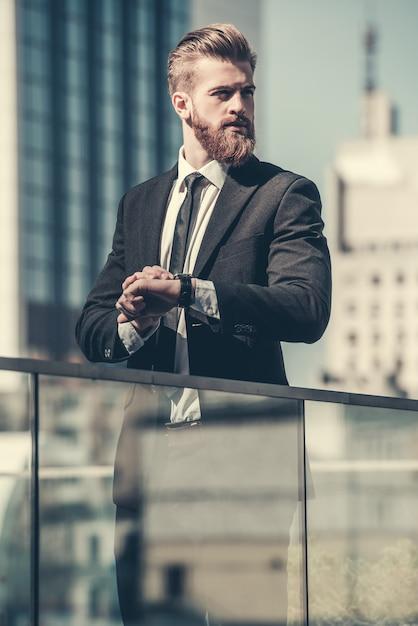 L'uomo d'affari barbuto in vestito classico sta distogliendo lo sguardo. Foto Premium