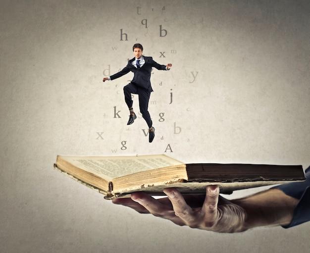 L'uomo d'affari che salta da un libro Foto Premium