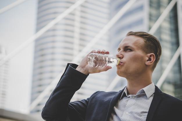 L'uomo d'affari di affari prende un'acqua potabile di resto davanti al centro di affari. Foto Gratuite