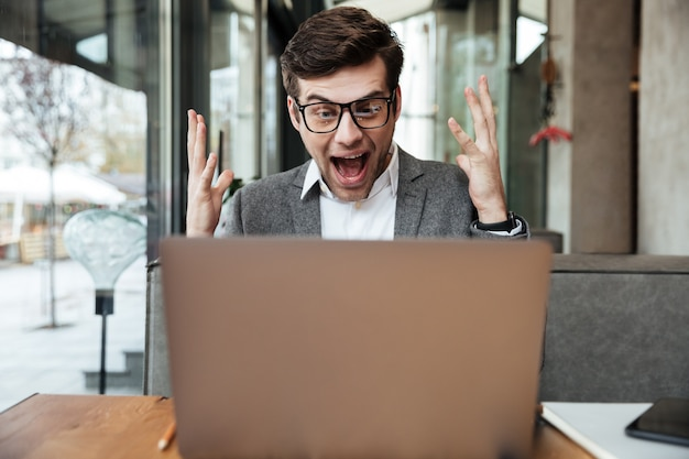 L'uomo d'affari di grido colpito in occhiali che si siedono dalla tavola in caffè e si rallegrano mentre esaminano il computer portatile Foto Gratuite