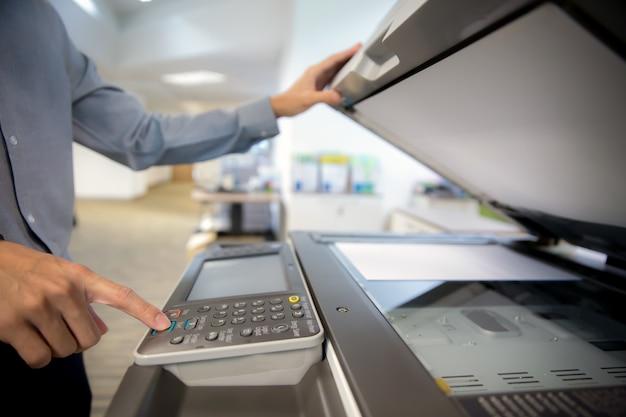 L'uomo d'affari è pulsante sul pannello della stampante, fotocopiatrice. Foto Premium