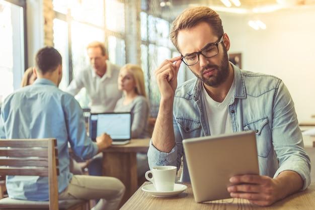 L'uomo d'affari in camicia e occhiali sta utilizzando la tavoletta digitale. Foto Premium