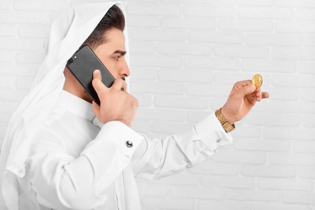 L'uomo d'affari in costume tradizionale considera il bitcoin dorato Foto Premium