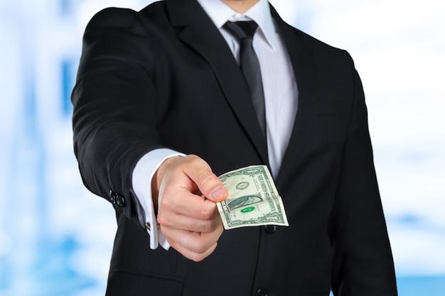 L'uomo d'affari irriconoscibile mostra la banconota del dollaro Foto Premium