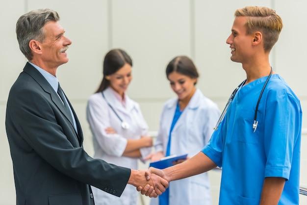 L'uomo d'affari maschio senior stringe i medici delle mani in ospedale. Foto Premium