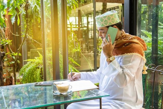 L'uomo d'affari musulmano pakistano usa il telefono cellulare astuto e scrive sul taccuino Foto Premium