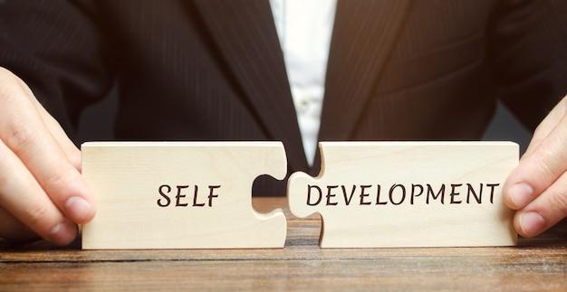 L'uomo d'affari raccoglie i puzzle sviluppo personale. Foto Premium