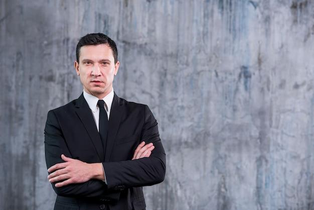 L'uomo d'affari sicuro con le armi ha attraversato l'esame della macchina fotografica Foto Gratuite