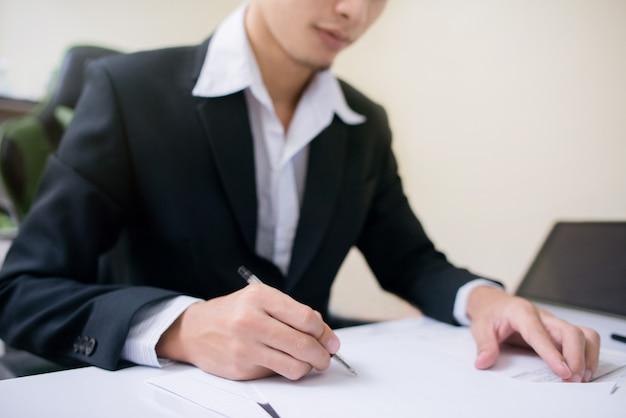 L'uomo d'affari sta firmando allo strato di carta. Foto Premium