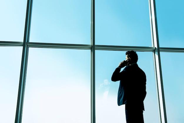 L'uomo d'affari sta guardando da una finestra panoramica. Foto Premium