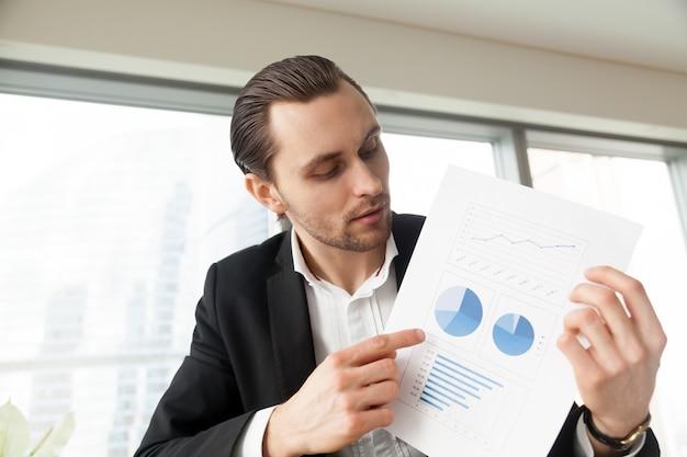L'uomo d'affari tiene il documento con il infographics Foto Gratuite
