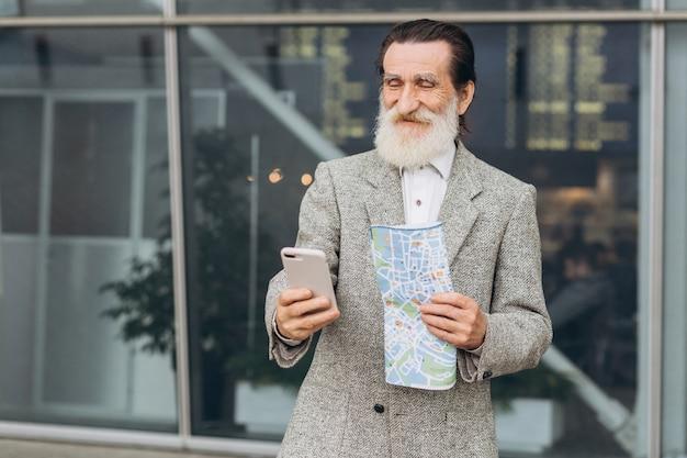 L'uomo dalla barba grigia senior che guarda lo smartphone e sorridere sta camminando lungo la costruzione dell'aeroporto Foto Premium