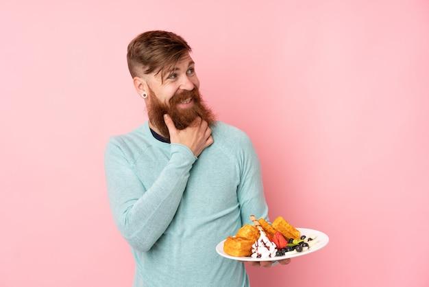 L'uomo della testarossa con la barba lunga che tiene le cialde sopra la parete rosa isolata che pensa un'idea e che guarda il lato Foto Premium