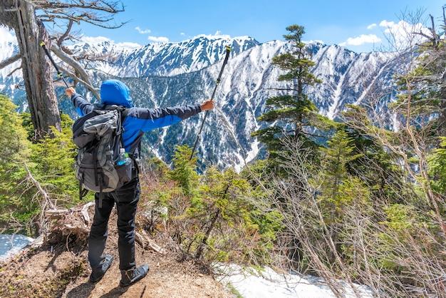 L'uomo della viandante tiene il palo di trekking e la mano di diffusione quando vede la catena montuosa della neve al punto di vista. Foto Premium