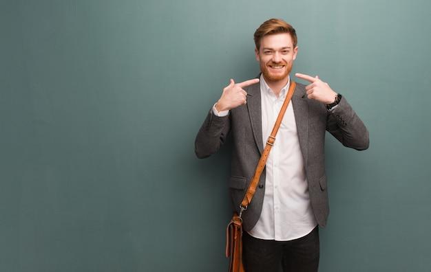 L'uomo di affari della giovane testarossa sorride, indicando la bocca Foto Premium